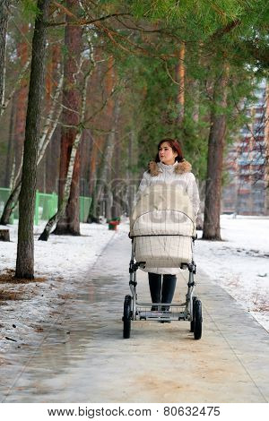 Young mother pushing pram in park winter