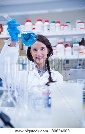 Chemist raising beaker of blue liquid in lab