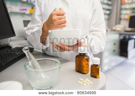 Junior pharmacist mixing a medicine at the hospital pharmacy