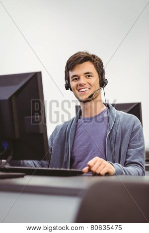 Student sitting at the computer room wearing headset at the university