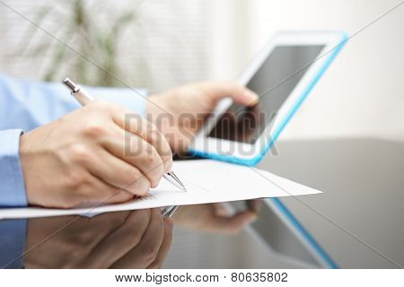 Businessman Is Filling Report After Reading Instruction On Tablet Pc