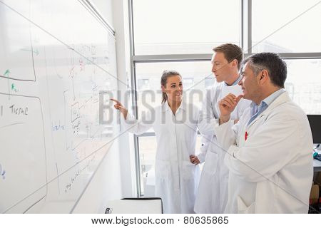 Science students and lecturer looking at whiteboard at the laboratory
