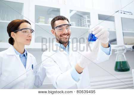 science, chemistry, technology, biology and people concept - young scientists holding flask with reagents and making test or research in clinical laboratory