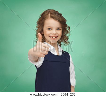 people, gesture, children, school and happiness concept happy little school girl showing thumbs up over green chalk board