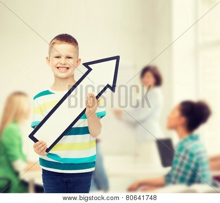 advertising, direction, education, teamwork and childhood concept - smiling little boy with white blank arrow pointing up over in classroom