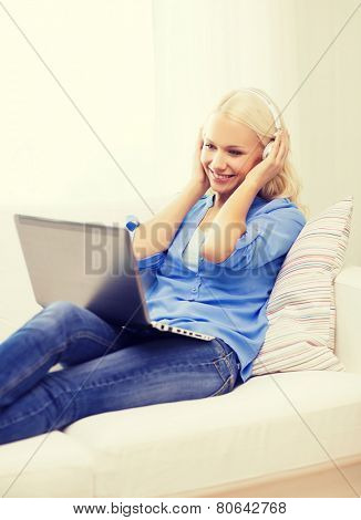 home, music, technology and internet concept - smiling woman lying on the couch with laptop computer and headphones at home