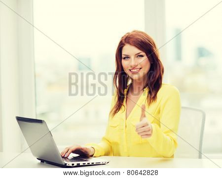 business, education and technology concept - smiling student with book laptop computer at school showing thumbs up