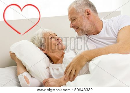 family, bedtime, valentines day, love and people concept - happy senior coupler lying in bad and talking at home with red heart shape