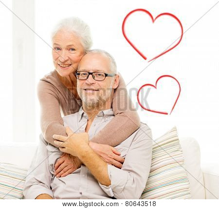 family, relations, love, age and people concept - happy senior couple hugging and holding hands on sofa at home with red heart shapes