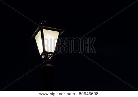 a classic lit street lamp post, against clear sky, night time.
