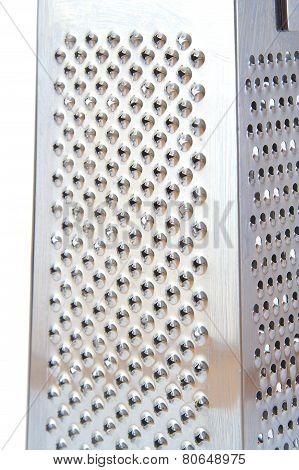Detailed view of metal grater on white background.