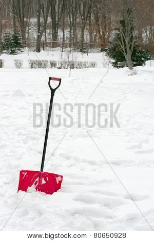 Red Plastic Shovel With Black Handle Stuck In Fluffy Snow.