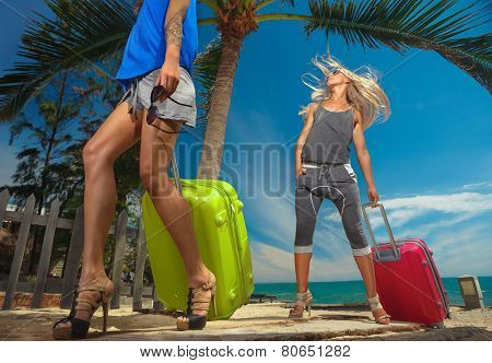 Young females  with a suitcases on the beach