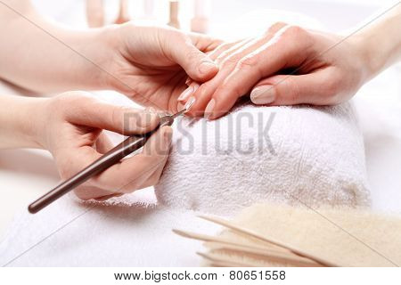 Manicure cutting skins woman to a beautician