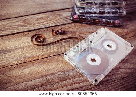 Audio cassette on the old wooden background. Toned image.