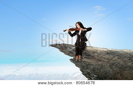 Young woman sitting on cliff edge and playing violin