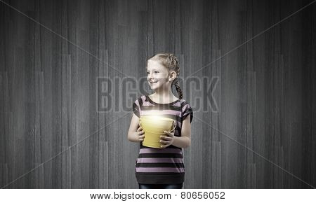 Cute girl with bucket trying to catch the sun