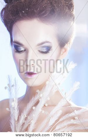 Beauty woman over blue winter background. Winter beauty woman. Snow queen. Make-up