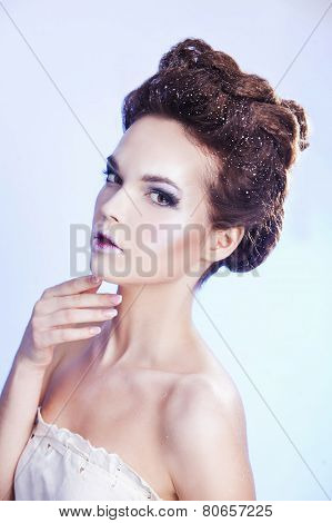 Beauty woman over blue background. Winter beauty model with luxury accessories. Snow queen. Make-up