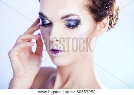 Close up portrait of woman with smoky eyes over blue winter background. Winter beauty woman. Snow qu