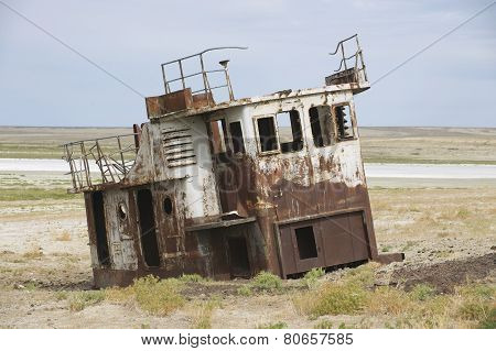 Rusted remains of fishing boats at the sea bed of the Aral sea Aralsk Kazakhstan.