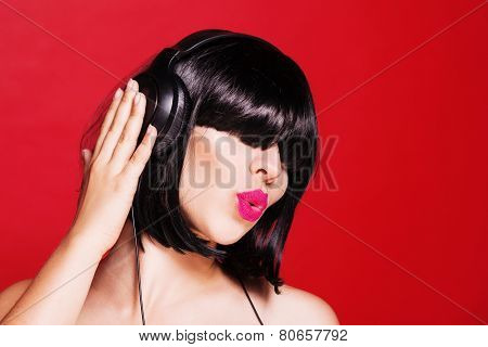 Dj woman listening to music on headphones enjoying a dance. Closeup portrait of beautiful girl with