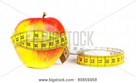 A yellow measuring tape wrapping red apple - healthy eating concept
