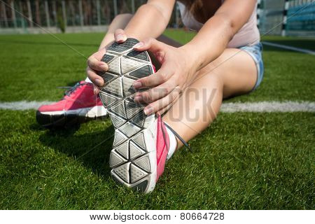 Young Woman Warming Up On Grass Before Running