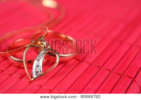 Two gold wedding rings and gold heart