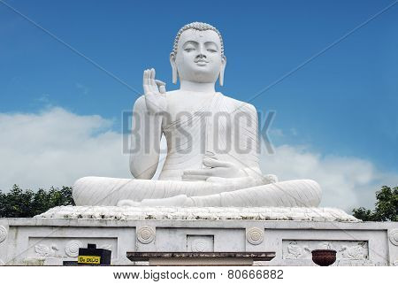 White statue of seated Buddha -Siddharta Gautama - with a raised right hand in a gesture of