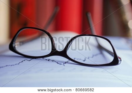 Glasses Are Laying On A Share Index
