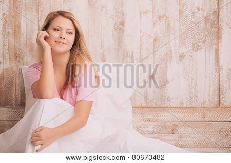 Young woman sitting in bed and touching face