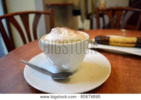 Delicious cappuccino in white cup on the wooden table