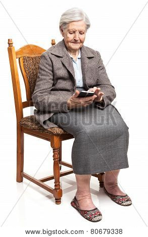 Senior woman using mobile phone sitting on chair