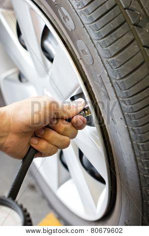 Man's Hand Checking Tyre Pressure.