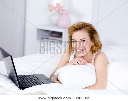 Smiling Woman Lying On A Bed With Laptop