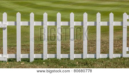 White Wooden Fence In Farm Field Marks For Land Property.