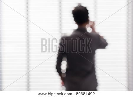 Blurred Picture Of Young Business Man Negotiate About His Task Near The Window.