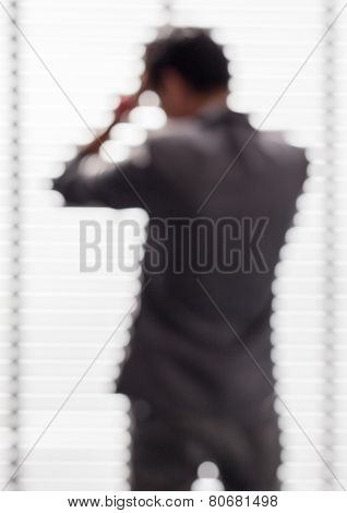 Blurred Picture Of Young Business Man Looks Seriously With His Negotiation With Phone.