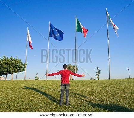 Flags on blue sky and man with open arms.