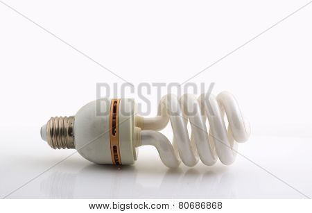 Used energy-saving lamp on a white table
