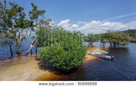 Beach and boat in the middle of Rio Negro, Brazil