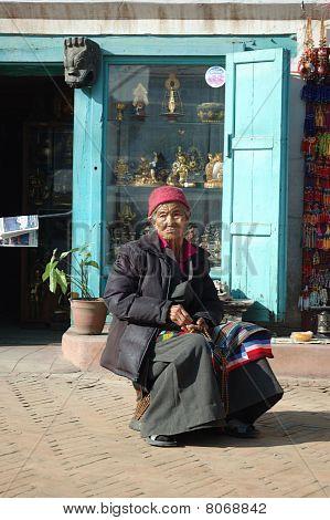 Old Tibetan Woman sitting near Swayambhunath Stupa,Kathmandu,Nepal