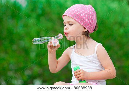 Cute Little Girl Blowing Soap Bubbles