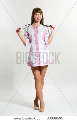 Young Nurse In With Stethoscope Standing Against Grey Background