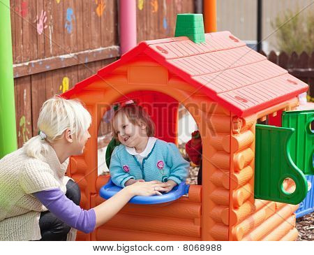 Sweet Girl Standing In A Small House At The Playground