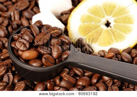 Coffee grains in a measuring spoon lemon and sugar