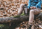 stock photo of thermos  - Hiker young woman holding a cup of tea or coffee and thermos in autumn forest - JPG