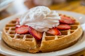 pic of whipping  - Golden brown waffle topped with sliced strawberries and whipped cream