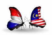 stock photo of holland flag  - Two butterflies with flags on wings as symbol of relations Holland and Malaysia - JPG